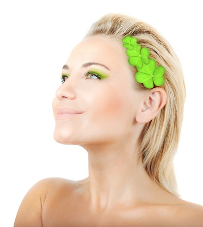 Beautiful woman with wreath of clover, fresh green plant leaves in blond hair, female face portrait isolated over white background, pretty girl with bright makeup, st. Patrick's day, spring holiday photo