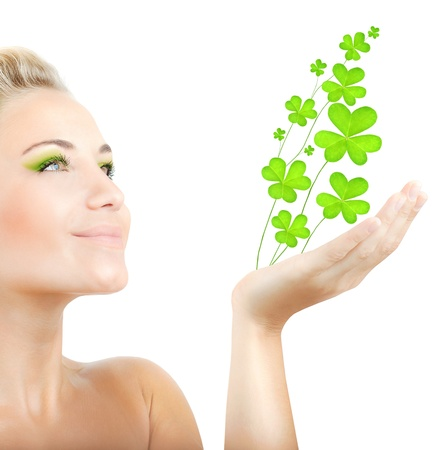 Beautiful woman holding fresh clover plant  in hand, sensual female portrait isolated on white background, cute girl with bright green makeup, st.Patricks day holiday Stock Photo