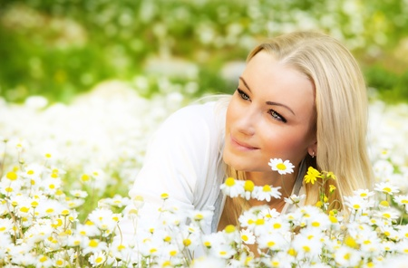 Beautiful woman enjoying daisy field, nice female lying down in the meadow of flowers, pretty girl relaxing outdoor, having fun, happy young lady and spring green nature, harmony & freedom concept Stock Photo - 12589157