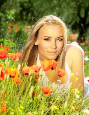 ケシを楽しんで美しい若い女の子の花のフィールド、屋外のポートレート、夏のお楽しみのコンセプトは、人々 農村レジャー女性新鮮な春の牧草地