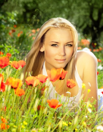 springtime: Young beautiful girl enjoying on the poppy flowers field, outdoor portrait, summer fun concept, beautiful woman relaxing in the floral garden, female at fresh spring meadow, people rural leisure