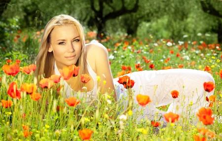 ragazze bionde: Giovane ragazza bella godendo sul campo di papaveri, fiori, ritratto all'aperto, divertimento concetto estate, bella donna di relax nel giardino floreale, femminile a prato fresca di primavera, tempo libero popolazioni rurali