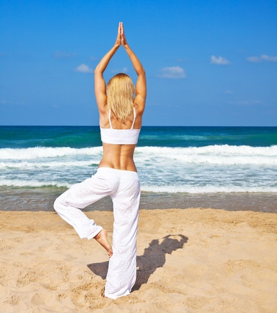 Healthy woman doing yoga posture, female exercising on the beach, slim sporty girl training body, lady workout, rear view,  fitness and health care concept photo