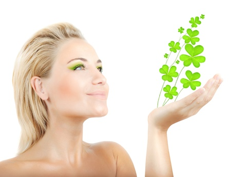 saint patrick's day: Beautiful woman holding fresh clover plant  in hand, sensual female portrait isolated on white background, cute girl with bright green makeup, st.Patricks day holiday Stock Photo