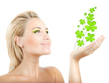 ragazze bionde: Bella donna tenendo pianta fresca trifoglio in mano, sensuale ritratto femminile isolato su sfondo bianco, ragazza carina con trucco verde brillante, giorno St.Patrick 's vacanza