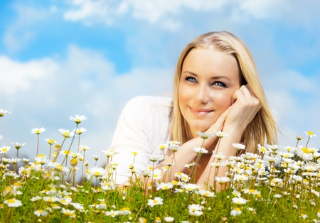 Beautiful woman enjoying daisy field and blue sky, nice female lying down in the meadow of flowers, pretty girl relaxing outdoor, happy young lady and green spring nature in harmony photo