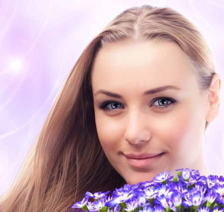 Beautiful female holding flowers, girl face with bouquet of spring plant, bunch of purple cornflowers, lovely woman with gift over pink abstract background photo