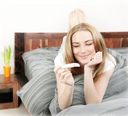 test de grossesse: Heureux, femme tenant test de grossesse, belle jeune femme à la maison couché dans le lit, dame saine vérifier résultat hormone, une nouvelle vie et le concept nouvelle famille Banque d'images