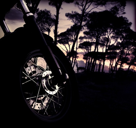 Motorbike wheel over forest sunset, selective focus on part of bike, shiny tire details, outdoor adventure ride, summer fun trip, freedom lifestyle concept photo