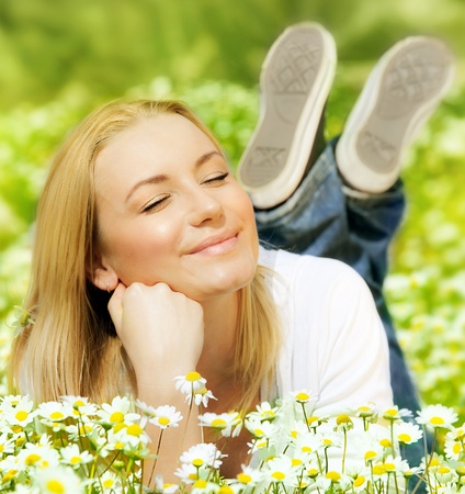 Beautiful woman enjoying daisy field, nice female lying down in the meadow of flowers, pretty girl relaxing outdoor, having fun, happy young lady and spring green nature, harmony and freedom concept Stock Photo - 12879952