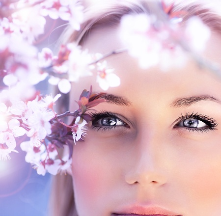 female face closeup: Sensual portrait of a spring woman, beautiful face, close up on blue eyes, female enjoying cherry blossom, dreamy girl with pink fresh flowers outdoor, seasonal nature, tree branch and natural beauty