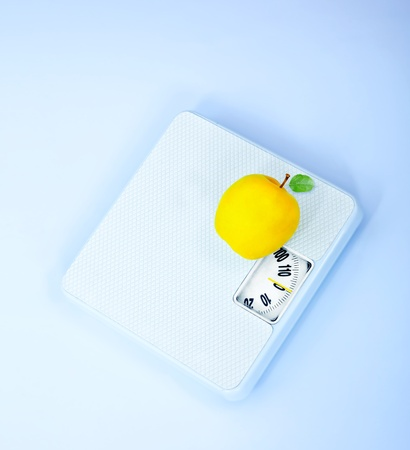 Scales and apple, body weight watching, conceptual image of dieting, calorie count, healthy lifestyle and shape control photo