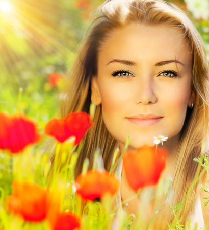 Closeup on beautiful woman face, female enjoying flower field, lovely girl at spring outdoor vacation, nice model relaxing at floral poppy garden, gorgeous model over natural bakground at sunny day Stock Photo