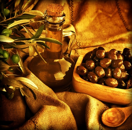 Grunge background, food still life, old style image of olives and olive oil, homemade traditional Mediterranean salad dressing, harvest