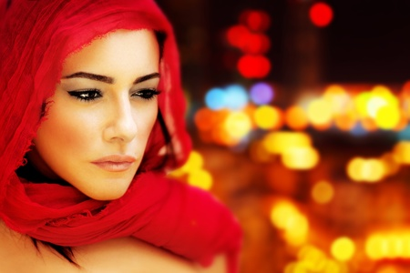 Beautiful Arabic woman wearing red scarf, stylish female face portrait over night city,  blur lights abstract  background, serious expression, stunning sensual beauty, model on the street photo