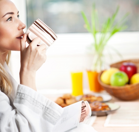 breakfast: Beautiful calm young woman having morning coffee, relaxing hot drink, happy female holding cup of tea, pretty blond girl eating and drinking healthy food at home, health care and dieting concept