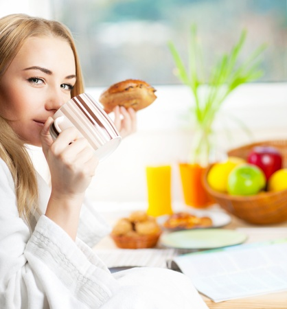 Beautiful calm young woman having morning coffee, relaxing hot drink, happy female holding cup of tea, pretty blond girl eating and drinking healthy food at home, health care and dieting concept photo