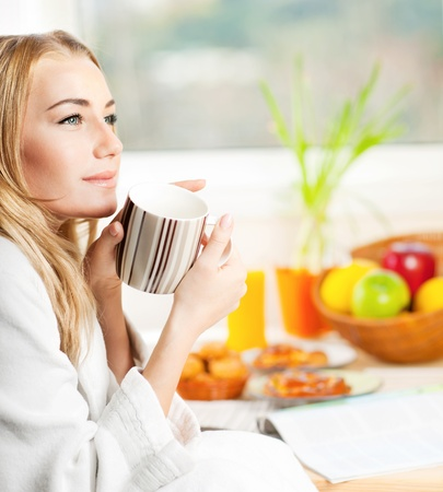 woman drinking coffee: Beautiful calm young woman having morning coffee, relaxing hot drink, happy female holding cup of tea, pretty blond girl eating and drinking healthy food at home, health care and dieting concept