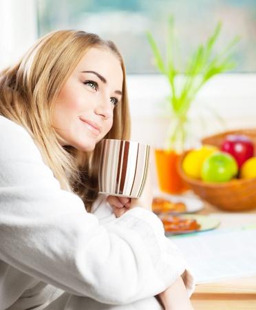 Schöne ruhige junge Frau mit Kaffee am Morgen, Entspannung Heißgetränk, glücklich Buchsenhalteblock Tasse Tee, hübsches blondes Mädchen essen und trinken gesunde Ernährung zu Hause, Gesundheits-und Diät-Konzept Standard-Bild
