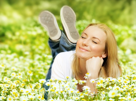 Beautiful woman enjoying daisy field, nice female lying down in the meadow of flowers, pretty girl relaxing outdoor, having fun, happy young lady and spring green nature, harmony and freedom concept photo