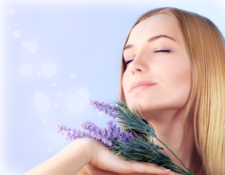 fragrant: Young woman enjoying lavender flower scent, close up on clean skin female face, sensual girl at spa aromatherapy, health and beauty treatment, wellness concept  Stock Photo