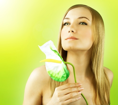 Fresh female face portrait, beautiful model holding calla flower, perfect skin girl over green spring background, zen relaxing woman, spa and health care concept photo