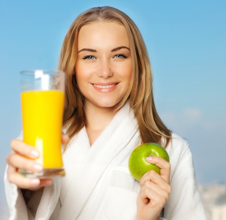 Healthy lovely young woman dieting, beautiful girl holding orange juice and green fresh apple fruit, happy smiling female portrait outdoor over blue sky background, nutrition and wellness concept photo