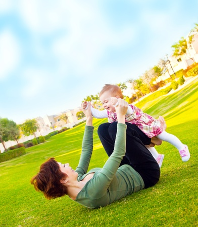 Mother and cute baby daughter playing outside at summer backyard, young woman with little girl, female holding child, beautiful mommy and cute kid lying on the grass, happy family in nature concept photo