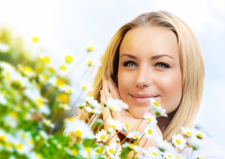 enjoying life: Beautiful woman enjoying daisy field and blue sky, nice female lying down in the meadow of flowers, pretty girl relaxing outdoor, happy young lady and green spring nature in harmony Stock Photo