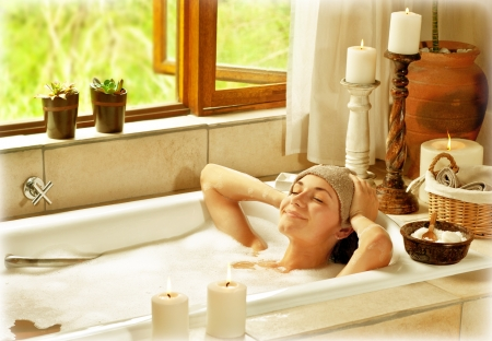 tomando: Woman taking bath, happy female relaxing at spa resort, young healthy girl at vacation, lady lying down in hot water, travel to luxury spa