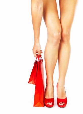 Beautiful female legs with red high heels holding shopping bags isolated on white background, money spending concept photo