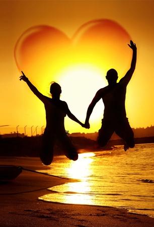 manos levantadas al cielo: Saltando feliz pareja de jóvenes, de la mano con forma de corazón en el cielo, símbolo de la felicidad, la familia jugando al aire libre, la puesta de sol en la playa, unas divertidas vacaciones romántica luna de miel, el concepto de amor