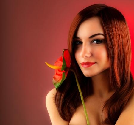 Sexy pelo rojo mujer de celebración cala flor, la glamorosa muchacha aislada sobre fondo rojo, dama elegante, sesión de moda femenina en el estudio de interiores, retrato hermoso rostro de primer plano