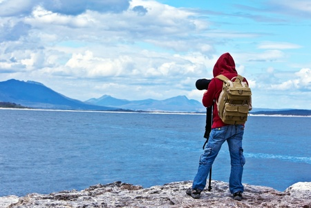 Wildlife photographer traveler enjoying ocean view from top of the mountain, backpacker hiking and taking pictures of South African landscapes, safari tour vacation, adventure and freedom concept  photo