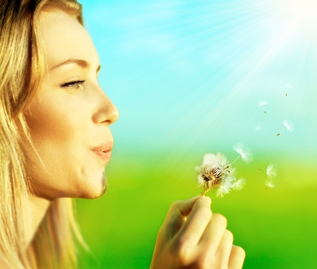 wish: Happy beautiful woman blowing dandelion over blur background, having fun and playing outdoor, teen girl enjoying nature, summer vacation and holidays, young pretty female holding flower, wish concept