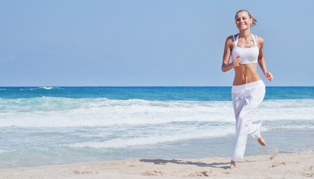 Healthy woman running on the beach, girl doing sport outdoor, happy female exercising, freedom, vacation, fitness and heath care concept with copy space over natural background photo