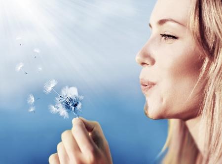 Hermosa mujer feliz que sopla el diente de león sobre fondo de cielo, divertirse y jugar de la muchacha al aire libre, adolescentes disfrutando de la naturaleza, las vacaciones de verano y las vacaciones, joven y bonita flor femenina celebración, desea concepto