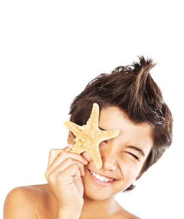 Happy face cute boy with starfish, closeup portrait of preteen brunette child, male kid model having fun, isolated on white background, summer travel and beach vacation photo