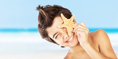 child model: Happy face cute boy with starfish on the beach, closeup portrait of preteen brunette child, male kid model having fun outdoor, summer travel and beach vacation Stock Photo