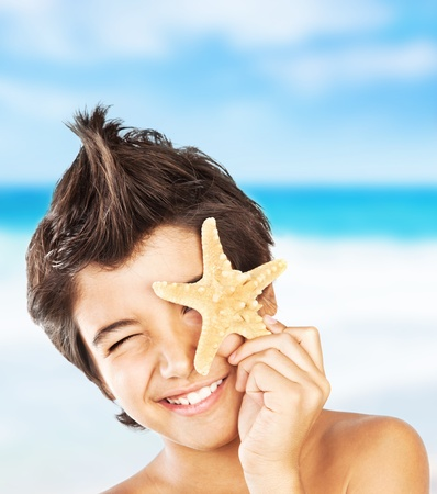 Happy face cute boy with starfish on the beach, closeup portrait of preteen brunette child, male kid model having fun outdoor, summer travel and beach vacation photo