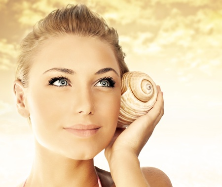 Beautiful woman face over beach sunset, lovely lady portrait with seashell, female enjoying nature sounds, sexy girl outdoor over sky, summer vacation and spa relaxation Stock Photo - 13284861