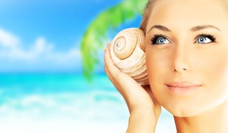 personas escuchando: Hermosa mujer disfrutar de la playa, closeup retrato rostro de mujer, niña feliz celebración de concha de mar, relajarse en la naturaleza, viaje de vacaciones de verano y el concepto de relajación spa Foto de archivo