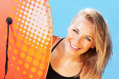 Happy surfer beautiful teen girl laughing, pretty female holds bodyboard, young healthy woman playing surf sport, big smile facial expression, summer outdoor beach leisure fun and vacation photo