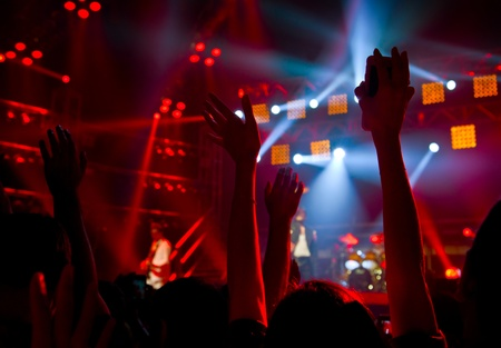 Disco party concert with large group of happy dancing people, silhouette of hands up in the air over blur red colorful stage lights, active lifestyle entertainment, music nightclub, night life concept Stock Photo - 13373037
