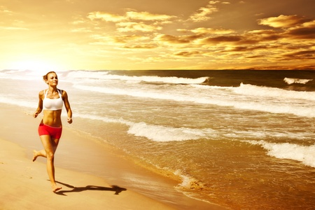 Healthy woman running on the beach, girl doing sport outdoor, happy female exercising, freedom, vacation, fitness and heath care concept with copy space over natural warm sunset background photo