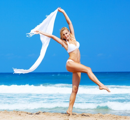 Jumping & dancing happy girl on the beach, fit sporty healthy sexy body in bikini, woman enjoys wind, freedom, vacation, summertime fun concept Stock Photo - 13525797