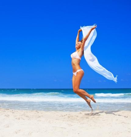 幸せな女の子、ビーチ、ビキニ、フィット スポーティな健康的なセクシーな体にジャンプ女性は風、自由、休暇、夏の楽しみを楽しんでコンセプト
