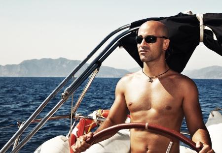 hombre sin camisa: Hombre guapo muscular en el timón, navegando en el mar Mediterráneo, viajando por el mundo en velero, modelo masculino en el yate de lujo, vacaciones de deporte acuático, verano al aire libre Foto de archivo