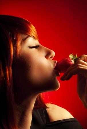 labios sexy: Impresionante mujer sexy, joven hermosa que come el perfil de la fresa, rostro de mujer, de cerca retrato con los ojos cerrados, el pelo rojo elegante de la moda y el maquillaje de color rojo los labios, la expresi�n del deseo, la pasi�n y el amor Foto de archivo