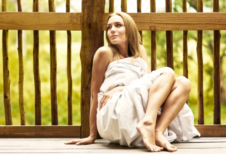 Young woman relaxing outdoor, sexy female sitting on the tropical terrace wrapped in bed sheet, calm pretty girl enjoying spa hotel resort, sensual shy romantic lady, vacation and health care concept photo